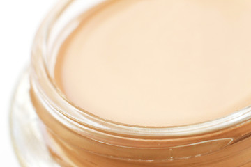 Pink tonal cream in glass jar close-up fragment