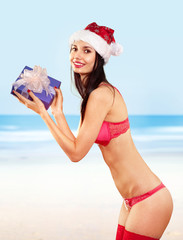 mrs claus with gift on beach