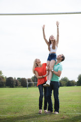 Mother and father lifting their daughter up to reach a goal.