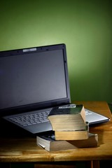 Stack of books and a Computer laptop