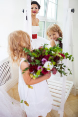 Smiling happy bride and a flower girl indoors