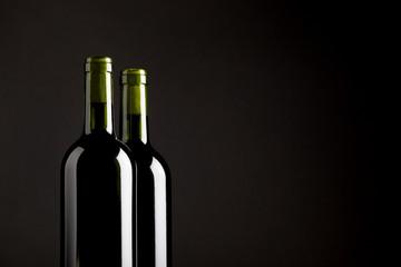 Rotweinflaschen vor dunklem Hintergrund