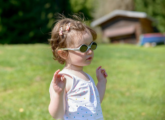 a little girl in the garden with sunglasses