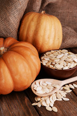 Pumpkins and seeds on wooden background
