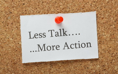Less Talk, More Action Reminder on a cork notice board