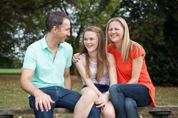 Loving Family having fun at  a bench in a park