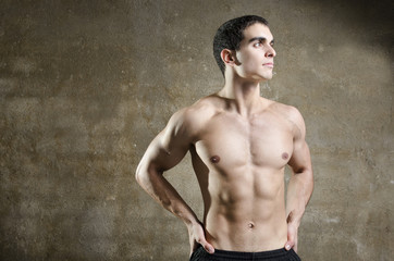 Young fitness man posing on dirty wall background