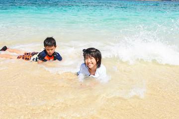 海辺で寛ぐ笑顔の姉弟