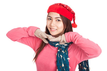 Asian girl smile with red christmas hat with both hands under ch