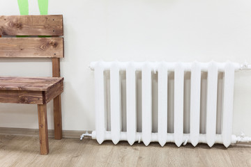 White iron radiator of central heating is near wooden bench