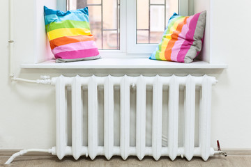 White radiator of central heating is in room under window