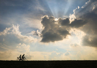 two bikers - two persons riding bike in front of a dramatic sky