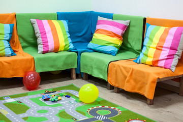 Interior with colorful wood sofa covered color blankets nursery