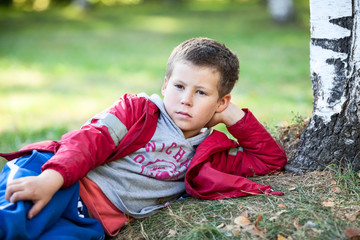 Young boy in red jacket resting on autumn grass in park