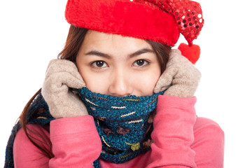 Happy Asian girl with red christmas hat and scarf feel cold