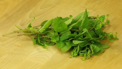 Bunch of mint rotates on a wooden boards background