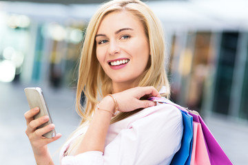 Woman with shopping bags and mobile phone