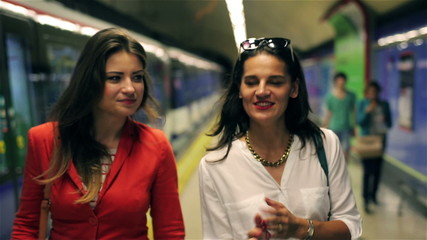 Women talking and walking on the metro station, steadycam shot