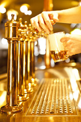 gold beer in the hand and beer taps
