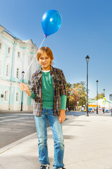 Boy with blue flying balloon standing on street