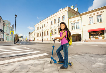 Asian girl with long hair stands on scooter