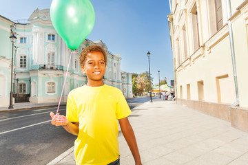 Happy African boy in yellow T-shirt with  balloon