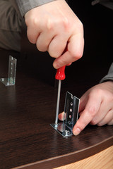 Screwing screws with a hand screwdriver, mount furniture fitting