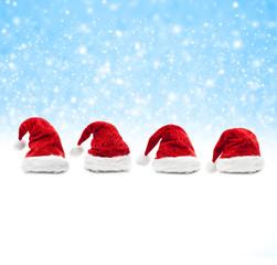 Weihnachtsmützen vor Blauem Schneehintergrund