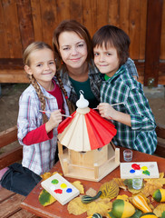 Woman and kids preparing a bird house in autumn