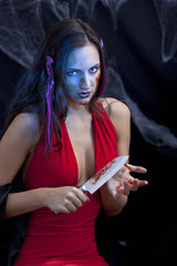 Foxy halloween woman or vampire with bloody knife
