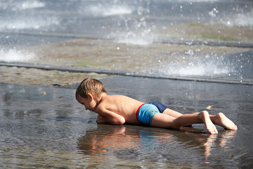 Little boy lying in puddle