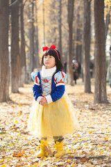 little girl dress in snow white costume in forest