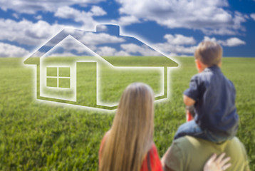 Young Family in Grass Field with Ghosted House in Front