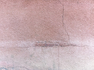 Old cracked  plastered wall painted pink