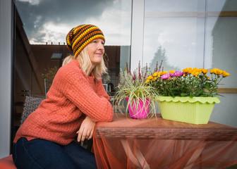 Frau auf dem Balkon am Tisch im Herbst