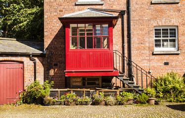 Courtyard with redbrick house and iron steps leading to a red po