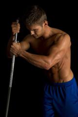 man fitness no shirt on black side light look down flex