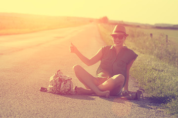 Traveler woman hitchhiking along lonely road in summer sunset