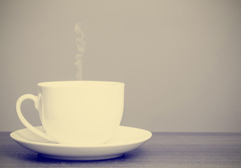 White cup and saucer on wooden table with retro filter effect