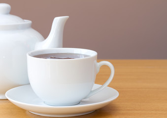 Cup of tea with teapot on a table