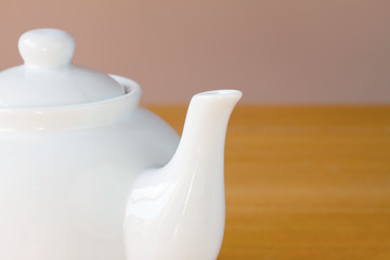 White teapot on a wooden table