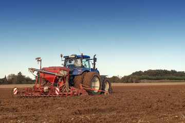 tractor seeding in a field on blue sky background