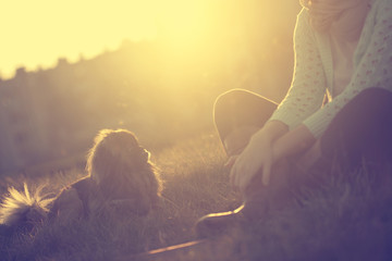 Woman relax with a dog in sunset