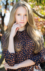Young beautiful girl touching her face, outdoor portrait