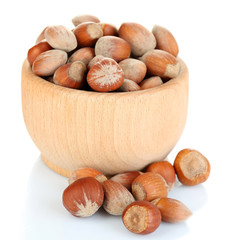 Hazelnuts in wooden bowl isolated on white