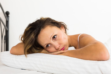 Upset woman laying in bed