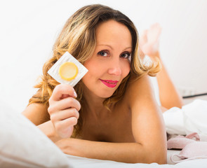Cheerful middle-aged woman showing contraceptive