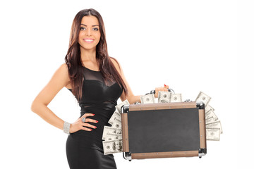 Attractive woman holding a briefcase full of money