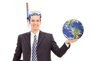 Businessman with diving mask holding the earth and standing