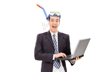 Excited businessman with diving equipment working on laptop